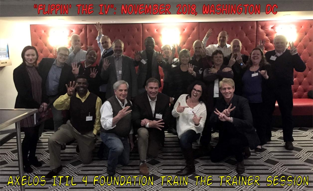 Attendees of the Axelos Train the Trainer session in November 2018 make a Number 4 hand gesture, as they